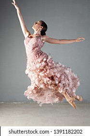 Classical ballet dancer jumping up effortlessly on stage with dress, performing arts indoors. Concept energy, power strength, lightness and harmony. Female beauty movement discipline training.