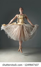 Classical ballet dancer on point shoes jumping up effortlessly on stage, indoors. Concept energy, power strength, lightness and harmony. Female beauty movement discipline training.