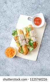 Classical banh-mi sandwich with sliced grilled pork tenderloin, shredded carrots and peeled cucumbers, jalapeno peppers and cilantro