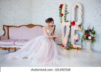 Classical beauty. Beautiful young woman with stylish brunette hair and elegant dress resting in luxury white classic room interior. Spring portrait of elegant girl.