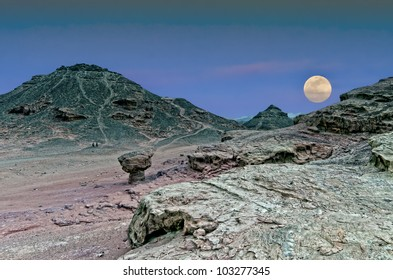 Classical biblical landscape with rise of supermoon in desert of the Negev, Israel