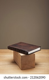 A classical brown diary with wood object on the desk.