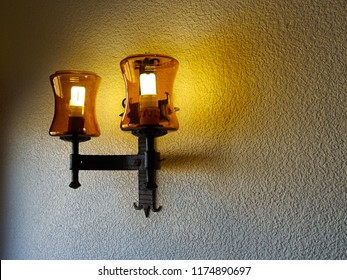 Classical design vintage style wall lamp creates warm light on a wall.