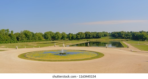 Classical French style gardens with lakes and fountains layed out in a geometrical style of Chantilly castle on a sunny day, Oise, France, designed by Le Nôtre at the end of the 17th century
