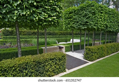 A classical garden with an avenue of yew, box and hornbeam leading to a water feature and sculpture