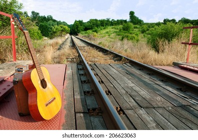 Classical guitar on the railway line illuminated by the setting sun 1