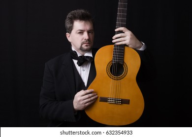 Classical guitarist dressed black suit with musical instrument