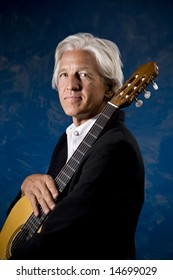 Classical Guitarist with his Instrument in front of a Blue Wall