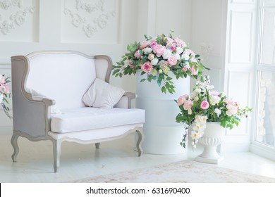 Classical interior with sofa. White room with sofa and two beautiful bouquets with roses, tulips and other flowers and greenery near it