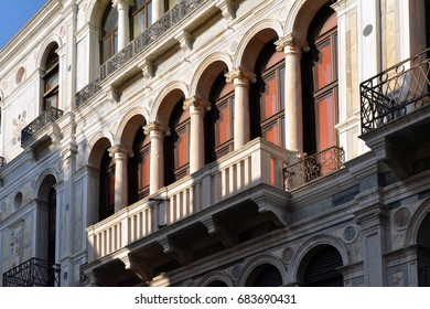 Classical Italian marble building facade with columns, arches and balcony