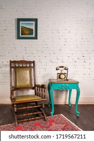 Classical leather rocking chair, wooden green vintage table, and antique golden telephone set in living room with white bricks wall and parquet floor