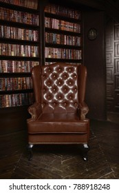 Classical library room with leather armchair, wooden table and bookcase