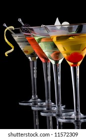 Classical martini in chilled glass over black background on reflection surface, garnished with fresh blackberry, maraschino cherry, marinated pearl onoions, olive and lemon twist.