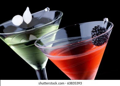 Classical martini in chilled glass over black background on reflection surface, garnished with fresh blackberry and marinated pearl onions. Most popular cocktails series.
