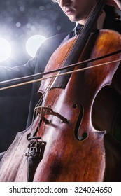 Classical music. Cellist playing classical music on cello on black background