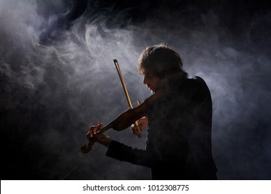 Classical musician violinist with a musical instrument violin, shot in Studio on black background