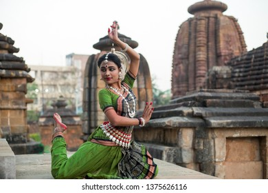 Classical odissi dancer wears traditional costume and posing in front of Mukteshvara Temple,Bhubaneswar, Odisha.