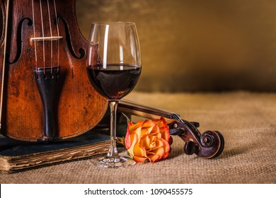 Classical old, used violins detail with red wine glass