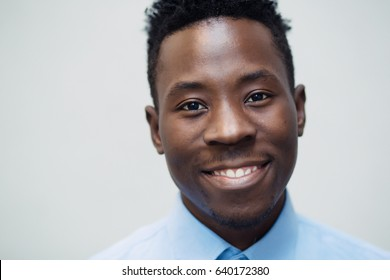 Classical portrait of smiling african american man in blue shirt at grey wall background