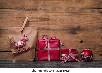 Classical red christmas gifts wrapped in paper with handmade sewed rocking horse and clothes peg.
