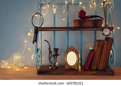 Classical shelf with vintage male objects and blank frame with gold garland lights. Ready to put photography