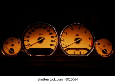 Classical sport dashboard, includes speedometer, tachometer, fuel, and temperature controls with chromed rings. Lights, oil pressure and battery are turned off. you can see sunlight at dusk reflect
