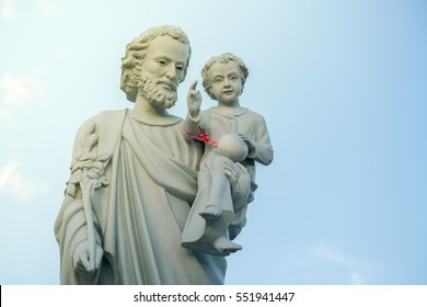 classical statue of Saint Joseph with child Jesus on blue sky. Joseph is a figure in the Gospels, the husband of Mary, mother of Jesus and is venerated as Saint Joseph in the Catholic Church.