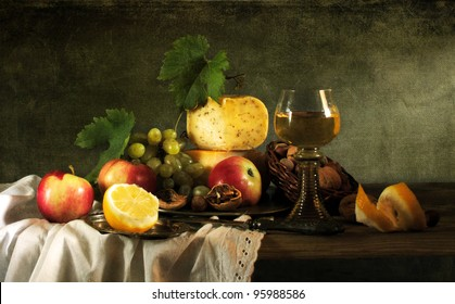 Classical still life with fruit, cheese, nuts and wine