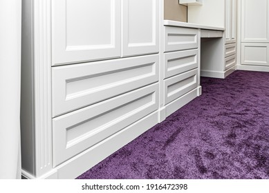 Classical style wardrobe with writing desk and drawers on a bright purple carpet in a bright room low angle view