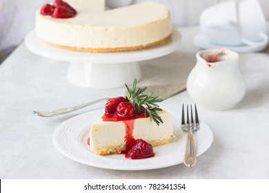 Classical vanilla cheesecake (New York cheesecake) with strawberry sauce and rosemary on white plate and light background
