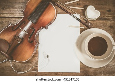classical violin, blank white paper & a cup of tea on wooden table
