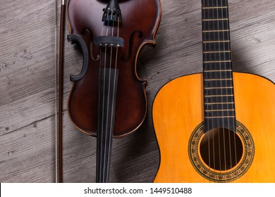 Classical violin and guitar on wooden background. Traditional musical instruments