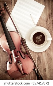 classical violin, music sheet & keys signature floating in a cup of coffee on wooden table