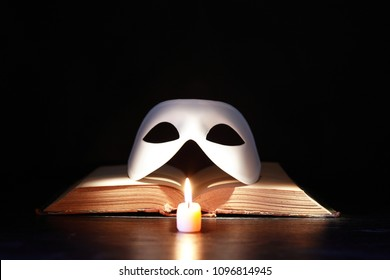 Classical white Venetian mask on old book near lighting candle against dark background
