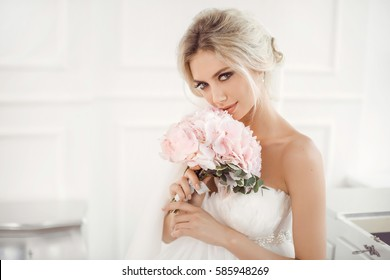 Classical young gourgeous bride. Studio interior fashion shot of fashion model in wedding dress with bouquet of flowers sitting in white room. Blonde woman portait with profeshional make-up and