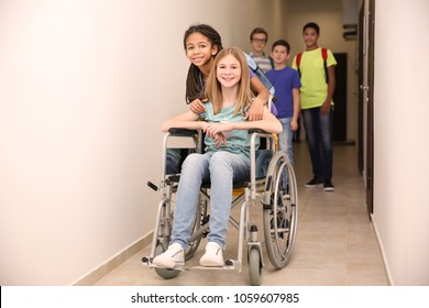 Classmate helping girl in wheelchair at school corridor