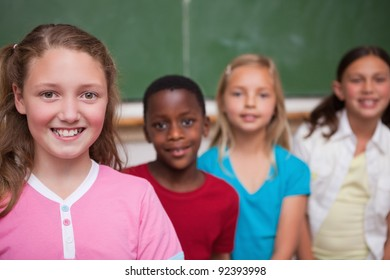 Classmates posing in a row in a classroom