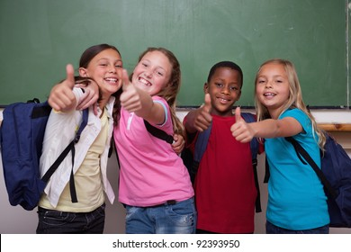 Classmates posing with the thumb up in a classroom