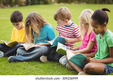 Classmates sitting in grass and reading books on campus