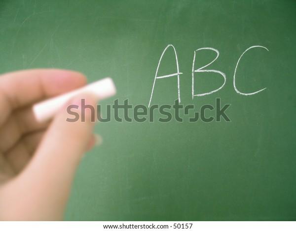 Classroom chalkboard .. hand with chalk. Focus on chalkboard.