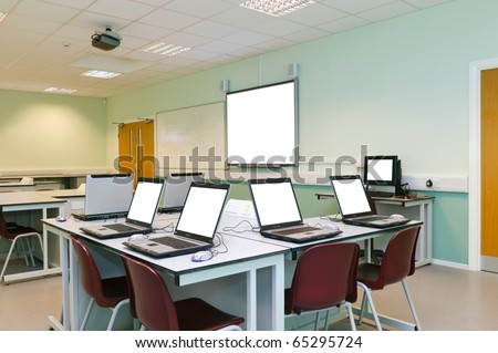 An IT classroom laptops on the desks and an interactive white board with blank screens to add your own image or text