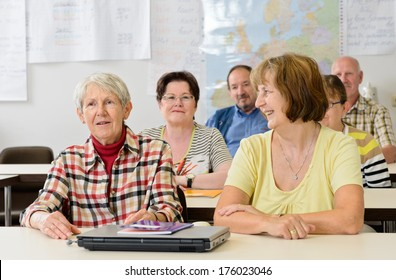 A classroom with older persons sitting at desks.