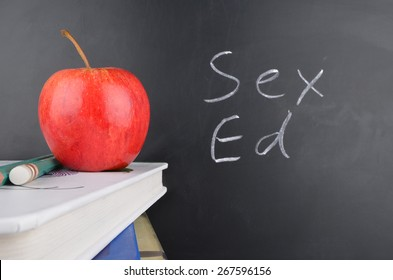 Classroom with red apple,books and handwriting in white chalk on blackboard saying sex education