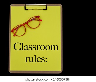 Classroom rules are written in black text on a yellow piece of construction paper on a wooden clipboard on an isolated black ground and red eyeglasses.