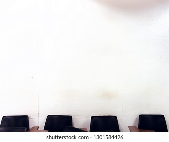 Classroom wall with four desks in front