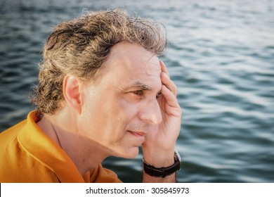 Classy  40 years old sportsman with three-day beard and salt and pepper hair wearing an orange polo shirt while he is thinking in front of the sea