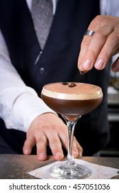 classy bartender suit garnish martini espresso cocktail drink white foam coffee bean on top bar counter