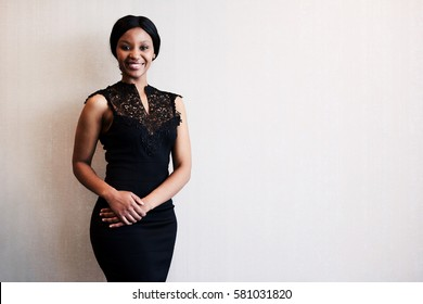classy black woman smiling into the camera while posing in a beautiful black dress against a textured beige wall, with excitement visible in her facial expression.