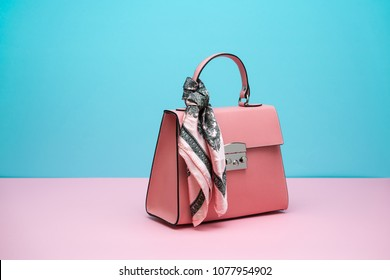Classy coral leather female bag with a silk scarf on the pink surface on the cyan background in the studio. Closeup. Horizontal.