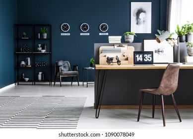 Classy, dark blue home office interior for a global businessman with elegant furniture and a computer on a wooden desk